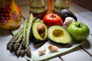 Asperagus, avacado, tomatos, and garlic on a counter