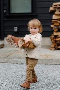 Girl child holding firewood