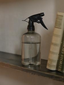 Clear glass spray bottle on a book shelf
