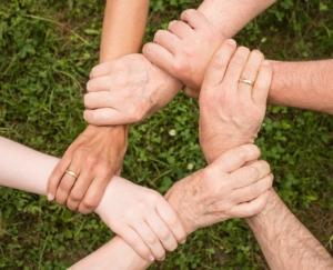 six hands forming a hexagon handshake